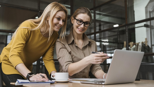 young-smiley-businesswomen-working-with-laptop-desk_23-2148824883
